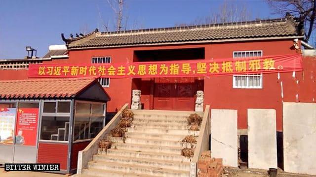 Une banderole sur laquelle est écrit « Résistez résolument aux xie jiao, et laissez-vous guider par la pensée de Xi Jinping sur le socialisme pour une nouvelle ère » est accrochée devant le temple de Beigongzhuang.