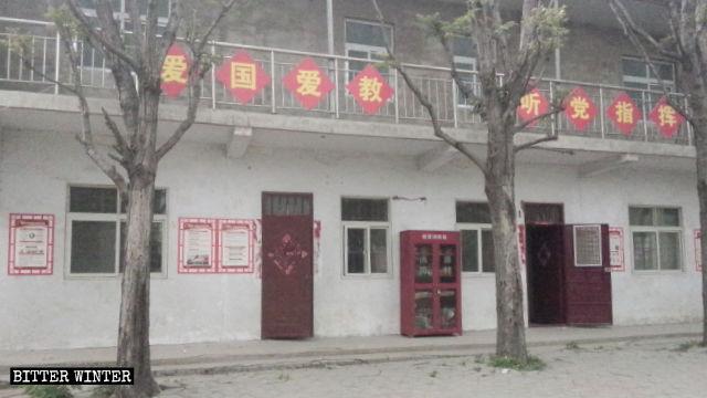 Les huit caractères chinois signifiant « Aimez votre pays, aimez votre religion et obéissez aux ordres du Parti » sont affichés sur la rambarde de l'église.