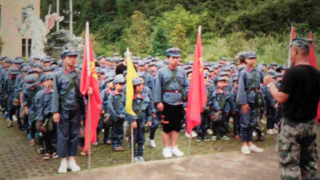 Des élèves en uniforme de l'Armée populaire, portant des sacs à dos sur lesquels sont imprimés le portrait du président Mao et le slogan « Servir le peuple ».