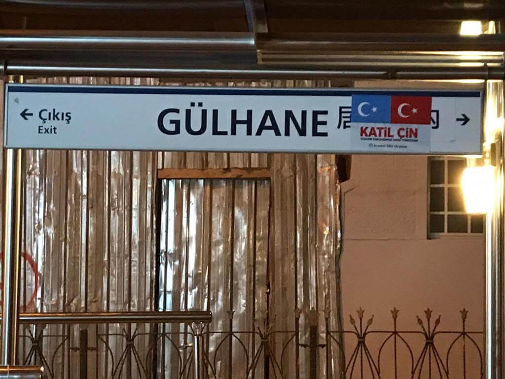 Panneau en mandarin de la station de tramway de Gülhane avec les drapeaux du Turkestan oriental et de la Turquie et les mots katil çin signifiant « Chinois assassin ! ».