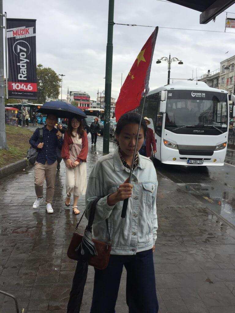 Le drapeau rouge chinois flotte haut dans les rues d'Istanbul alors qu'une guide touristique emmène son groupe de touristes dans les anciens bazars.