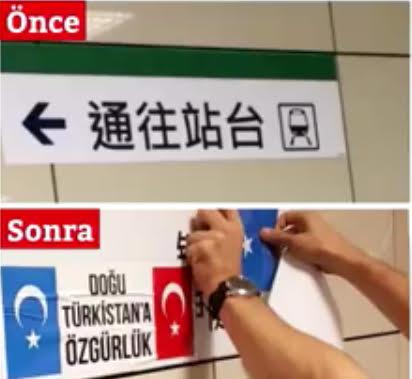 En-dessous du panneau en mandarin indiquant la direction du quai du tramway, un sympathisant turc accroche les drapeaux du Turkestan oriental et de la Turquie avec du ruban adhésif.